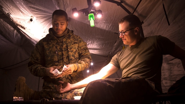Seaman Damon Oda-Kauhola prepares to place an IV for Petty Officer 3rd Class Cory Richards Jan. 6 in a medical tent at Combined Arms Training Center Camp Fuji, Japan. Corpsman must undergo an additional, more rigorous training program that prepares them to perform their duties under more strenuous conditions to better support the operational forces. Oda-Kauhola and Richards are corpsmen with 3rd Battalion 5th Marine Regiment; currently assigned to 3rd Marine Division, III Marine Expeditionary Force under the unit deployment program. Oda-Kauhola is a Kapolei, Hawaii, native. Richards is an Amsterdam, N.Y., native.