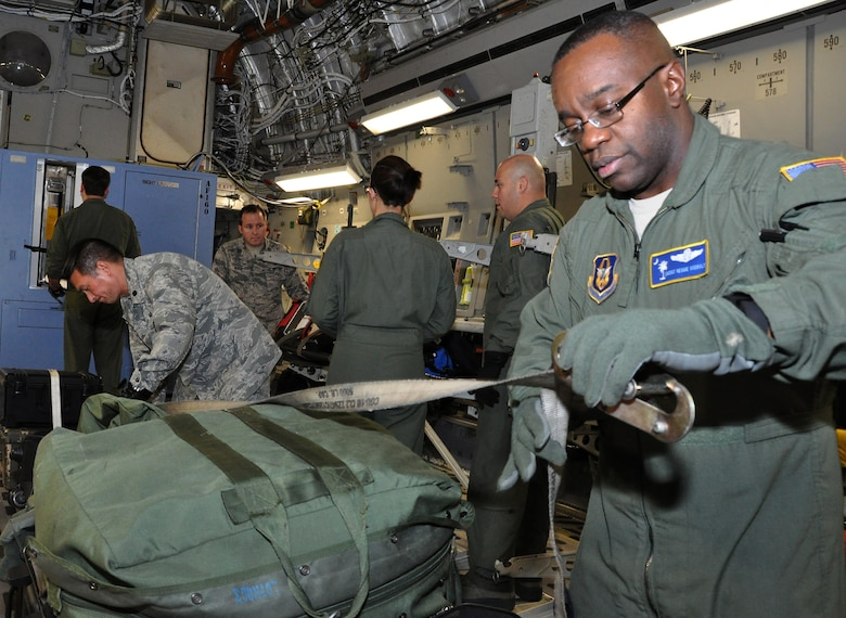 Ministry of presence - Chaplain (Lt Col.) Ronald Apollo (left), 315th Airlift Wing, assists Chief Master Sgt. Reggie Godbolt, 300th Airlift Squadron loadmaster superintendent, as he ties down bags on a recent training mission to Ramstein AB, Germany. (U.S. Air Force Photo by Maj. Wayne Capps)