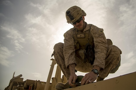 U.S. Marine Corps Cpl. Nicholas Orbik, engineer with Special Purpose Marine Air-Ground Task Force-Crisis Response-Central Command, prepares a truck to transport Alaskan barriers at Al Taqaddum Air Base, Iraq, Jan. 8, 2016. The 12-ton barriers are placed around structures to reinforce them and provide protection from shrapnel. Advise and assist sites, like Al Taqqadum Air Base, are an integral part of Combined Joint Task Force – Operation Inherent Resolve's multinational effort to increase the military capacity of Iraqi Security Force personnel to defeat the Islamic State of Iraq and the Levant. (U.S. Marine Corps photo by Cpl. Akeel Austin/Released)
