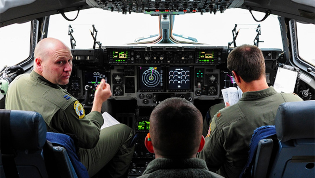 Capt. Brandon Reynolds, a pilot with the 300th Airlift Squadron at Joint Base Charleston, S.C., receives information from an aerial port member while on a training mission at Ramstein Air Base, Germany, Jan. 23, 2016.