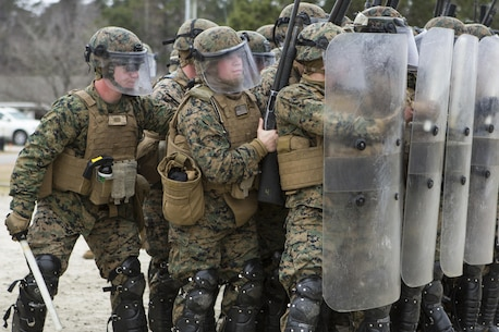 U.S. Marines with Battalion Landing Team, 1st Battalion, 6th Marine Regiment, 22nd Marine Expeditionary Unit (MEU), hold riot shields to prevent injury during a simulated riot at Camp Lejeune, N.C., Jan. 22, 2016. The Marines participated in the course to ensure mission readiness and to improve their ability to maintain control during a riot. (U.S. Marine Corps photo by Cpl. John A. Hamilton Jr./Released)