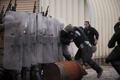Marines with Battalion Landing Team 1st Battalion, 6th Marine Regiment, 22nd Marine Expeditionary Unit use riot shields to prevent a simulated attack during a non-lethal weapons course at Camp Lejeune, N.C., Jan. 22, 2016. The Marines participated in the course to ensure mission readiness and to improve their ability to maintain control during a riot. (U.S. Marine Corps photo by Cpl. Chris Garcia/Released)
