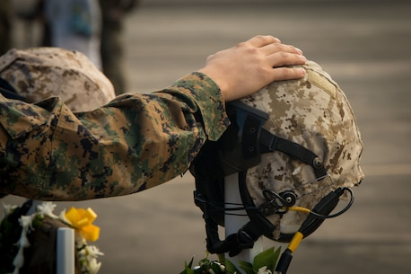 A Marine places his hand over the Kevlar of a battlefield cross during a memorial ceremony honoring 12 Marines from Marine Heavy Helicopter Squadron 463 aboard Marine Corps Air Station Kaneohe Bay, Jan. 22, 2016. Two CH-53E Super Stallion helicopters with HMH-463 were involved in an incident off the coast of North Shore, Oahu, Hawaii, Jan. 14.