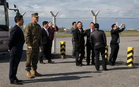 Col. Peter Lee, second from left, escorts members of the Liberal Democratic Party Youth Bureau of Gunma Prefecture to the flight line Jan. 25 on Marine Corps Air Station Futenma, Okinawa, Japan. During the visit, Lee explained the logistics and capabilities of the MCAS Futenma followed by a tour of the flight line. The members had the opportunity to witness an MV-22B Osprey landing on the flight line, and step off their tour bus to take photos. Lee is the commanding officer of MCAS Futenma.