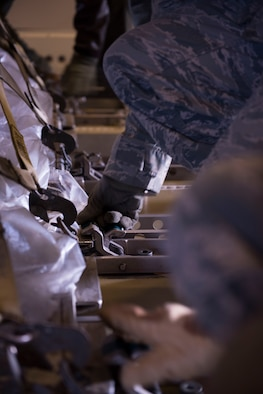 Airmen from the 366th Logistics Readiness Squadron secure latches on cargo in a KC-10 Extender from Travis Air Force Base, California, Jan. 23, 2016 at Mountain Home AFB, Idaho. The cargo will be delivered to Tyndall AFB, Florida, for Combat Archer and Combat Hammer. The exercise is designed to test each participating units' Weapon System Evaluation Program, determine reliability, evaluate capability and limitations, identify deficiencies, recommend corrective action and maintain combat readiness. (U.S. Air Force photo by Senior Airman Lauren-Taylor Levin/RELEASED)