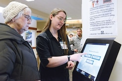 Trixy Buttcane, 673d Medical Support Squadron contract certified pharmacy technician, assists a patient navigating the new pharmacy kiosk system at the hospital on Joint Base Elmendorf-Richardson, Alaska, Jan. 19, 2015. For the first three months, technical assistants helped patients learn the new system to effectively transition the populace to the change. (U.S. Air Force photo by Airman 1st Class Christopher R. Morales)