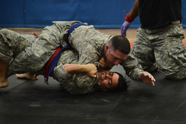 Two U.S. Army 743rd Military Intelligence Battalion Squadron soldiers battle for control during a combatives tournament at the Buckley Fitness Center Jan. 22, 2015, on Buckley Air Force Base, Colo. The army battalion hosts the tournament every year to hone hand-to-hand combat training techniques while engaging in friendly competition. (U.S. Air Force photo by Staff Sgt. Darren Scott/Released)