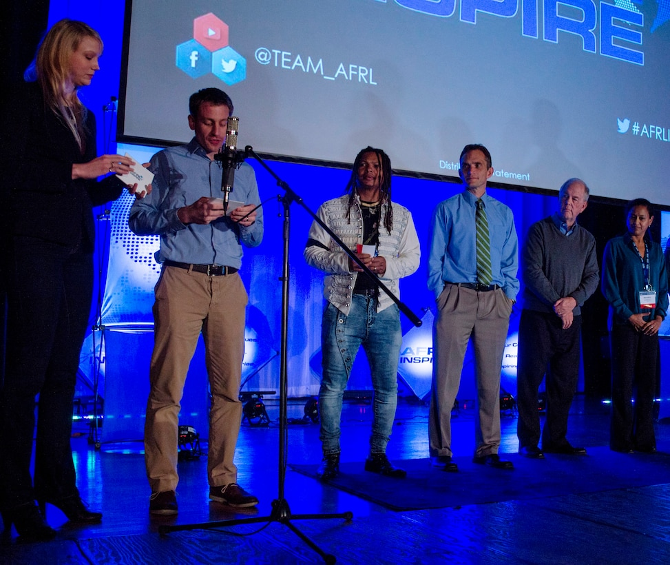 Kerianne Gross and Dr. Dan Berrigan (left), architects of AFRL Inspire, served as the event's emcees.  Also pictured are four presenters from the inaugural AFRL Inspire event. From left: Dr. Moriba Jah, Dr. Jeff Calcaterra, Dr. Robert Fugate, and Dr. Nandini Iyer. (U.S. Air Force photo / Mikee Huber)