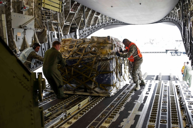 Airmen assigned to the New York Air National Guard's 105th Airlift Wing and Fresno ANG's 144th Fighter Wing, slide a pallet aboard a C-17 Globemaster III at the Fresno ANG Base, Jan. 21, 2016, in support of the 144th FW's participation in Red Flag 16-01. Red Flag is a realistic combat training exercise, which is hosted by Nellis Air Force Base, Nevada and the U.S. Air Force Warfare Center. The 105th AW airlifted 12 pallets and 29 personnel assigned to the 144th FW. (U.S. Air National Guard Senior Airman Klynne Pearl Serrano)