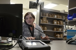 Jessica Holder, 673d Medical Support Squadron contract certified pharmacy technician, answers emails, phone calls, and questions at the new pharmacy window at the hospital on Joint Base Elmendorf-Richardson, Alaska, Dec. 23, 2015.  The new pharmacy windows provide more privacy between customers, and the waiting area window panels illustrate each animal-inspired entrance of the hospital. (U.S. Air Force photo by Airman 1st Class Christopher R. Morales)