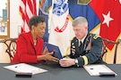 "Bernadette Gray-Little, University of Kansas chancellor, presents Maj. Gen. Wayne W. Grigsby Jr., 1st Infantry Division and Fort Riley commanding general, with a copy of a partnership resolution between their organizations Nov. 23 in Lawrence, Kansas. Grigsby said wherever he went in uniform, people always thanked him for what he does. ""Whenever I'm around educators, it's the other way around because you guys are the ones that are really transforming our country and transforming our youth through the headware,"" Grigsby said to KU officials and educators he met with on campus. ""You do that in your university each and every day. … I just wanted to personally thank each and every one of you for what you do for us. It's very important."""