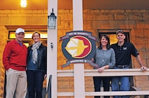 """Left to Right:  Command Sgt. Maj. Jonathan Stephens, Dawn Stephens, Lauren Bolen and Col. Thomas Bolen, 1st Infantry Division Artillery command team and their spouses, hung the DIVARTY crest on the Bolen home Nov. 20 at Fort Riley.  This is the first time the """"Drumfire"""" crest was placed on a """"Big Red One"""" quarters since the brigade deactivated on Feb. 15, 2006, at Warner Barracks, Bamberg, Germany.  The DIVARTY reactivated Oct. 16 at Fort Riley, and will support the division's mission readiness by standardizing artillery training, certifying and teaching sections and enabling higher-level exercises throughout the division."""