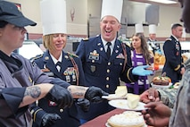 First Sgt. Terrina Anderson and Chief Warrant Officer 3 Jeffrey Price, 1st Infantry Division Band command team, help serve desserts Nov. 25 at Demon Diner dining facility at Fort Riley. As is tradition in units across the Army, senior leaders dress in their finest to serve meals to junior Soldiers and their families.