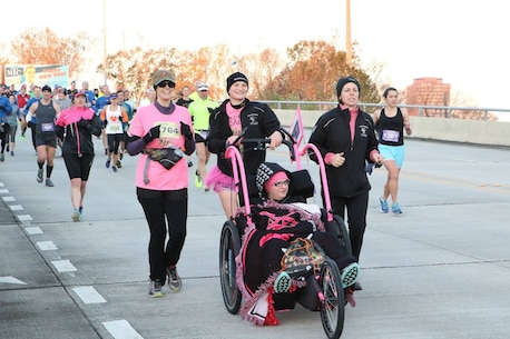Captain Danielle Falcon, Marine Corps Recruiting Station Baton Rouge executive officer, pushes a member of Ainsley's Angels of America during the Louisiana Half-Marathon on Jan. 17, 2016. Ainsley's Angels of America aims to build awareness about America's special needs community through inclusion in all aspects of life. The organization was started by Major Kim Rossiter who is currently stationed in Norfolk, Va. Major Rossiter's daughter, Ainsley, is a child with Infantile Neuroaxonal Dystrophy which is a rare terminal illness that progressively causes global paralysis. (U.S. Marine Corps photo by Sgt. Rubin J. Tan/Released)