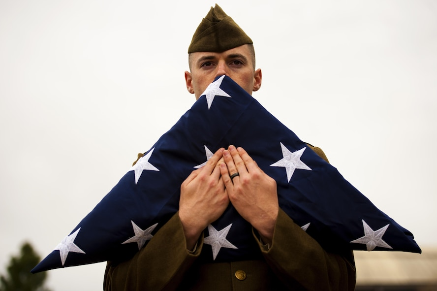 U.S. Air Force Senior Airman Austin T. Gregg, 17th Medical Support Squadron medical information systems technician, holds the American flag during the 75th Diamond Anniversary at the Norma Brown building on Goodfellow Air Force Base, Texas, Jan. 26, 2016. Honor guard members, dressed in uniforms from the 1940s, passed off the flag to a contemporary fitted honor guard to honor all generations of Goodfellow. (U.S. Air Force photo by Senior Airman Scott Jackson/Released)