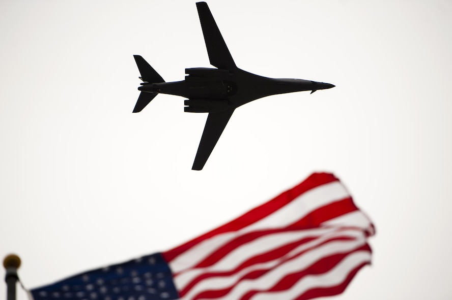 A Rockwell B-1 Lancer flies over the Norma Brown building during the 75th Diamond Anniversary ceremony on Goodfellow Air Force Base, Texas, Jan. 26, 2016. The B-1 flew over after a Vultee BT-15 Valient flew over. Both were symbolic; the vintage BT-15 representing the planes that Goodfellow pilots trained on, and the B-1 representing the intelligence support training the base now provides. (U.S. Air Force photo by Senior Airman Scott Jackson/Released)
