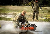On January 19, 2016 Second Lieutenant Matt Bergman, a student with Combat Engineer Officer's course 3-16 (CEO 3-16); uses a cut-off saw to aid in the repairing of a spall at the airfield damage repairs site located at Court House Bay, Camp Lejeune, N.C. A spall is known as pavement damage that is no more then 5 feet in diameter and does not penetrate into sub-grade material. Gunnery Sergeant Jessie McDonald, a Combat Engineer Instruction Company instructor; holds the saws cord while supervising the training.