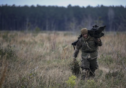 A Marine student undergoing the 2nd Marine Division Combat Skills Center's Pre-Scout Sniper Course departs a field following a stalking exercise at Camp Lejeune, N.C., Jan. 22, 2016. The DCSC offers several infantry-based courses to enhance the combat readiness of its Marines.  (U.S. Marine Corps photo by Cpl. Paul S. Martinez/Released)