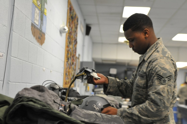 Senior Airman K'Shawn Joseph, 113th Operations Group Aircrew Flight Equipment technician, prepares pilots' equipment prior to a Familiarization Flight at Naval Air Station Joint Reserve Base New Orleans, La. The D.C. Air National Guard Airmen are participating in a two-week flying exercise titled Sentry Voodoo in New Orleans. (Air National Guard photo by Senior Airman Erica Rodriguez/Released)