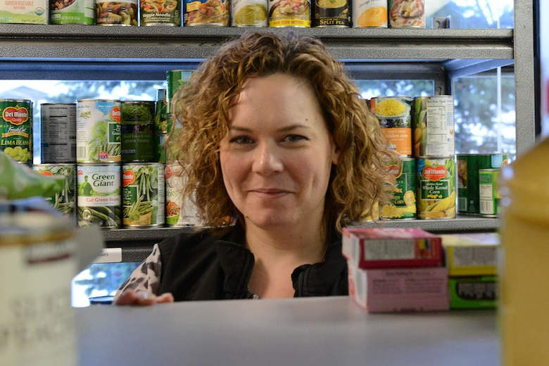 Lita McClain, marketing and public relations specialist for the Armed Services YMCA of Alaska, stocks available shelf space at the ASYMCA food pantry on Joint Base Elmendorf-Richardson, Alaska, Jan. 26, 2016. The food pantry is one of more than 20 programs offered by the ASYMCA, specifically designed to meet the needs of the JBER community. (U.S. Air Force photo by Airman 1st Class Javier Alvarez)