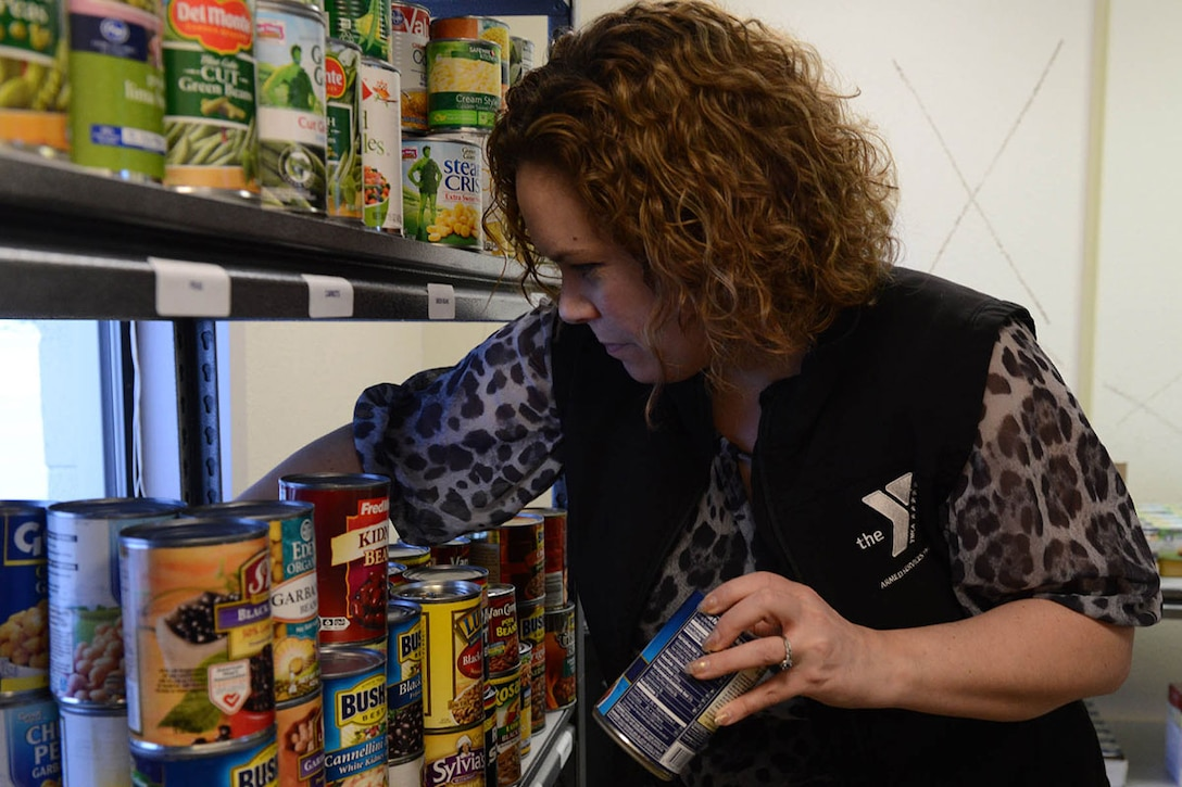 Lita McClain, marketing and public relations specialist for the Armed Services YMCA of Alaska, stocks shelves at the ASYMCA food pantry, on Joint Base Elmendorf-Richardson, Alaska, Jan. 26, 2016. In 2015, the ASYMCA food pantries provided an estimated 15,032 pounds of food to military families on the JBER and Fort Wainwright communities. (U.S. Air Force photo by Airman 1st Class Javier Alvarez)