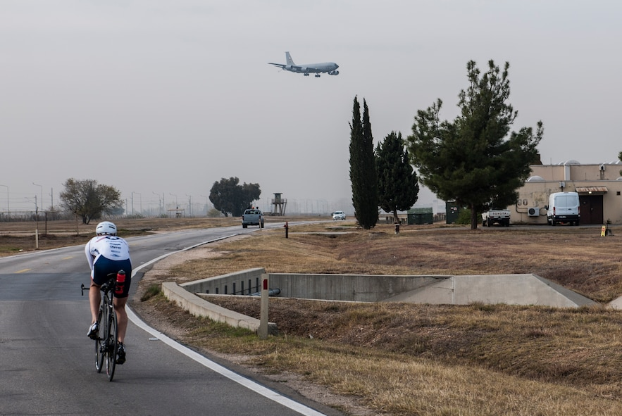U.S. Air Force Senior Master Sgt. Jason Chiasson, 39th Communications Squadron production superintendent, rides past the flightline Dec. 10, 2015, at Incirlik Air Base, Turkey. Chiasson, a member of the Air Force Cycling Team, regularly cycles a variety distances both indoors and outdoors to stay prepared for the races he will participate in as part of the cycling team. (U.S. Air Force photo by Senior Airman Krystal Ardrey/Released)