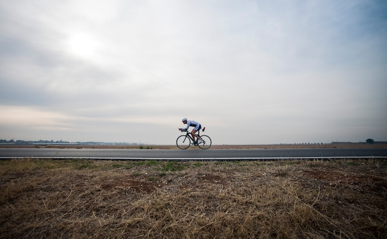 U.S. Air Force Senior Master Sgt. Jason Chiasson, 39th Communications Squadron production superintendent, rides around the flightline Dec. 10, 2015, at Incirlik Air Base, Turkey. Chiasson rode 25 miles on his lunch break as part of his training program for the Air Force Cycling Team. (U.S. Air Force photo by Senior Airman Krystal Ardrey/Released)