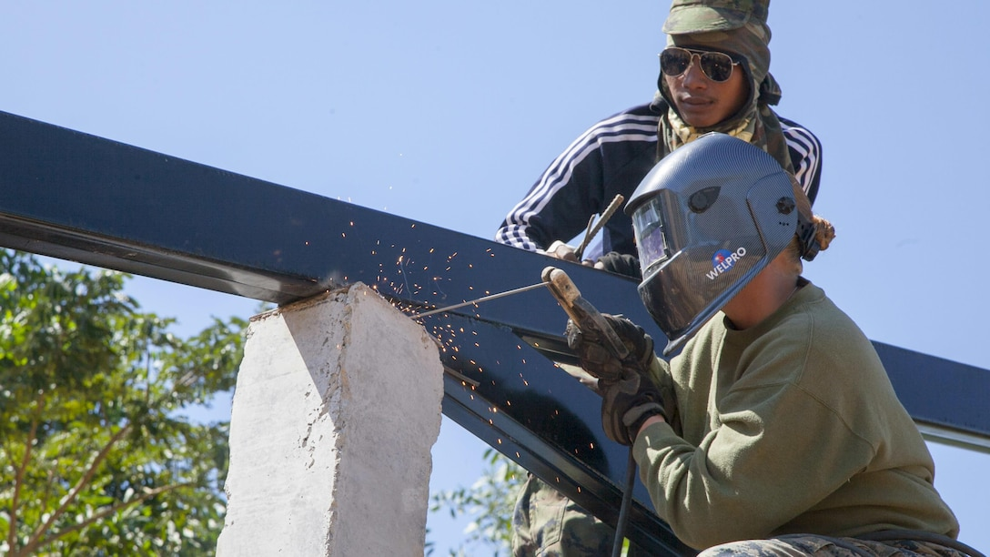 U.S. Marine Corps Cpl. Cami Snider, a Westerville, Ohio native, welds a tress onto a support column as Royal Thai Marine Corps Seaman Class Chainarong Kaewyongkot observes Jan. 23 at the Watkhunsong humanitarian civic action site, Chanthaburi, Thailand. The construction at Watkhunsong is one of six HCA sites in which the Thai, U.S. and partner nation's militaries will work together on HCA programs to support security and humanitarian interests of friends and partner nations during Cobra Gold 2016. The programs will improve the quality of life, as well as the general health and welfare of civilian residents in the exercise areas. Snider is a metal worker with Marine Wing Support Squadron 172, Marine Aircraft Group 36, 1st Marine Aircraft Wing. Kaewyongkot is with the Engineer Battalion, Marine Division, Royal Thai Navy.