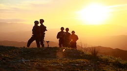 Marines look over the hill tops at their targets as the sun sets at Marine Corps Base Camp Pendleton, California, Jan. 13, 2016. The Marines are a mix of Joint Tactical Attack Controllers and Joint Fire Observers who are responsible for directing fires of artillery and aircraft. The Marines are with 1st Air Naval Gunfire Liaison Company, I Marine Expeditionary Force.