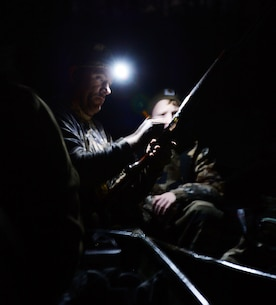Gunnery Sgt. David A. Kelley, assault amphibious vehicle technician, Marine Corps Systems Command, shows a young duck hunter how to properly load a shotgun during Marine Corps Logistics Base Albany's annual Youth Duck Hunt, Jan. 16.