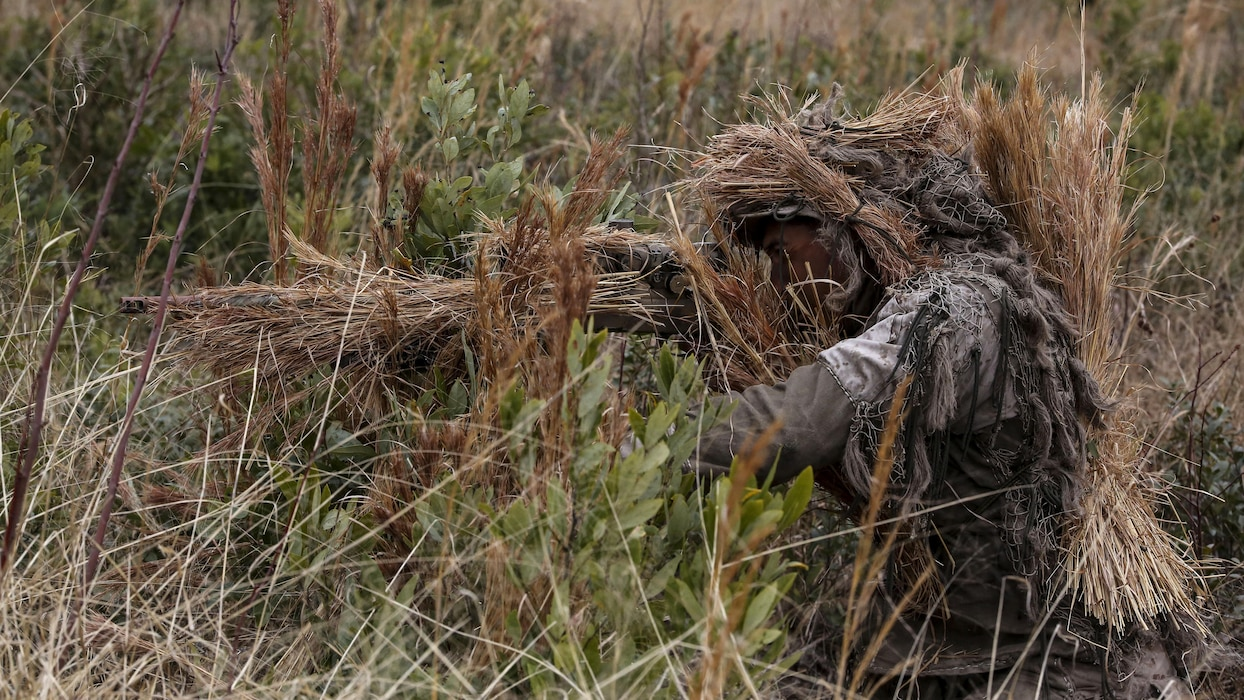 Corporal Brighten Bell, a student undergoing the 2nd Marine Division Combat Skills Center's Pre-Scout Sniper Course, acquires a target during a stalking exercise at Marine Corps Base Camp Lejeune, North Carolina, Jan. 22, 2016. The exercise required students to traverse approximately 1,000 meters of high grass and fire on a target, all without being detected.