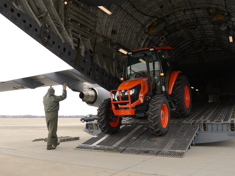 A tractor is loaded onto a C-17 Globemaster III at Niagara Falls Air Reserve Station, N.Y., January 9, 2016. The tractor is being transported to Dobbins Air Reserve Base. (Photo by U.S. Air Force Staff Sgt. Richard Mekkri/released)