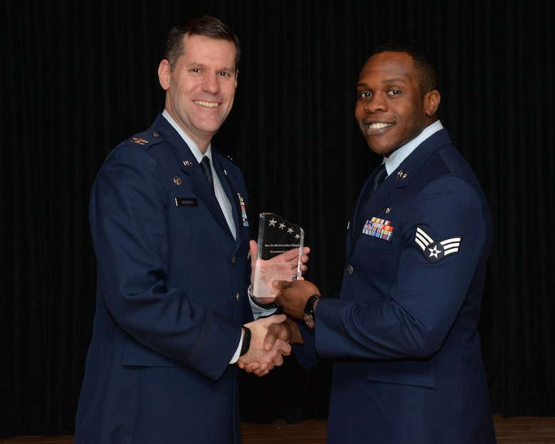 Col. John Devillier, 88th Air Base Wing commander, presents the 2016 Dr. Martin Luther King Jr. Humanitarian Award to Senior Airman Daniel Ononiwu, a public health technician with the 88th Aerospace Medicine Squadron, Public Health Flight. (U.S. Air Force photo/Michelle Gigante)