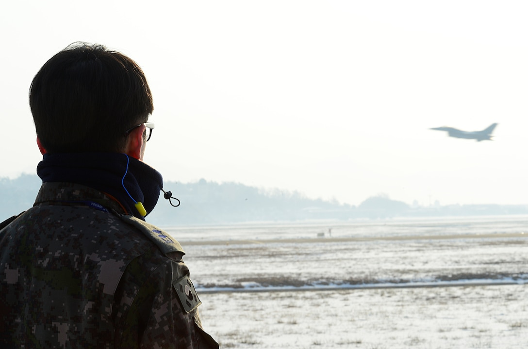 An airman from the Republic of Korea air force watches an F-16 Fighting Falcon from the 36th Fighter Squadron takeoff during Buddy Wing 16-1 at Seosan Air Base, ROK, Jan. 28, 2016. The Buddy Wing exercise is a combined fighter exchange program between the U.S. and ROKAF to promote solidarity and mutual understanding of all executed operations. (U.S. Air Force photo by Senior Airman Kristin High/Released)