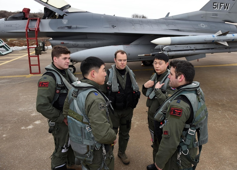 Pilots from the 36th Fighter Squadron, U.S. Air Force, and the 121st Fighter Squadron, Republic of Korea air force, communicate before takeoff during Buddy Wing 16-1 at Seosan Air Base, ROK, Jan. 28, 2016. The exercise, conducted throughout the year, is used to sharpen interoperability between the allied forces. (courtesy photo/Released)