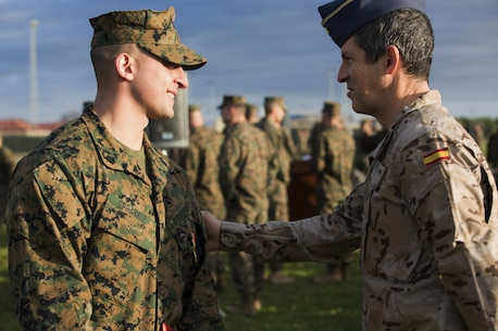 U.S. Marine Corps Sgt. Matthew A. Sprankle is congratulated by a Spanish Air Force Officer at Morón Air Base, Spain, Jan. 26, 2016, after receiving the Navy and Marine Corps Medal for saving a Senegalese man from drowning on last August. The award is the highest non-combative decoration for heroism awarded by the U.S. Department of the Navy.  (U.S. Marine Corps photo by Sgt. Kassie L. McDole/Released)