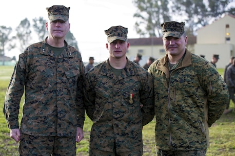 U.S. Marine Corps Maj. Gen. Niel E. Nelson, commander of U.S. Marine Corps Forces Europe and Africa, (left), and Sgt. Maj. William R. Frye, Sergeant Major of U.S. Marine Corps Forces Europe & Africa (right), pose for a photo with Sgt. Matthew A. Sprankle, after he received the Navy and Marine Corps Medal aboard Morón Air Base, Spain, Jan. 26, 2016, for saving a Senegalese man from drowning last August. The award is the highest non-combative decoration for heroism awarded by the U.S. Department of the Navy.  (U.S. Marine Corps photo by Sgt. Kassie L. McDole/Released)