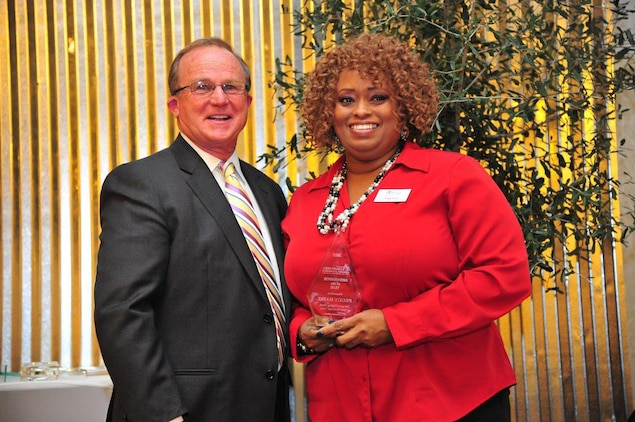 Peggy Haire, program analyst, Logistics Services Management Center, Marine Corps Logistics Command, receives the 2016 Ambassador of the Year award from Ed Newsome, incoming board chairman, Albany Area Chamber of Commerce, during the Albany Area Chamber of Commerce 106th annual meeting held at the Hilton Garden Inn and Conference Center in Albany, Georgia, Jan. 21.