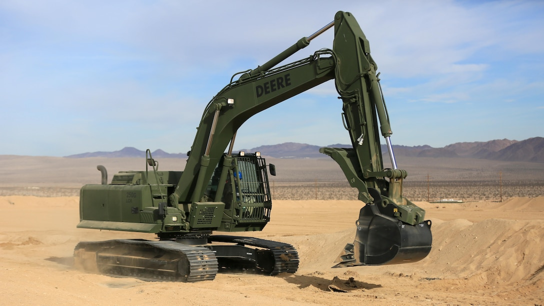 Staff Sgt. John Vasquez, heavy equipment operations chief, Marine Wing Support Squadron 374, maneuvers a John Deere 250 GR Hydraulic Excavator near the Strategic Expeditionary Landing Field, Jan. 22, 2016. The excavator enables Marines to fulfill critical engineering missions, including backhoe excavations, development of field fortifications, digging water and sewer lines, emplacement of culverts in-road, airfield construction and creating command bunkers.