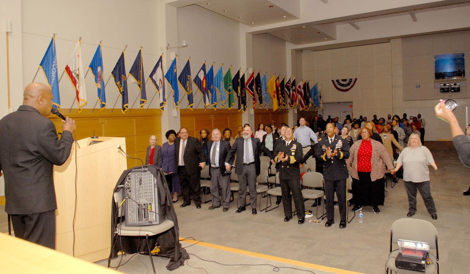 """DLA Troop Support and NAVSUP Weapons Systems Support employees sing """"We Shall Overcome"""" during a ceremony in honor of Civil Rights leader Dr. Martin Luther King, Jr. Jan. 21 in Philadelphia. Key Arts Production performed a multimedia presentation titled """"King's Dream"""" which outlined King's life from childhood, his leadership in the Civil Rights Movement and assassination in 1968."""
