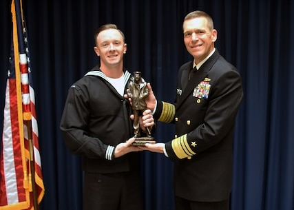 WASHINGTON (Jan. 21, 2016) Hospital Corpsman 1st Class Mark Francesco, from Atlantic City, N.J. receives a trophy from Vice Adm. Dixon Smith, commander of Navy Installations Command (CNIC) for his selection as 2015 CNIC Sailor of the Year. (U.S. Navy photo by Mass Communication Specialist 1st Class John Belanger/Released)