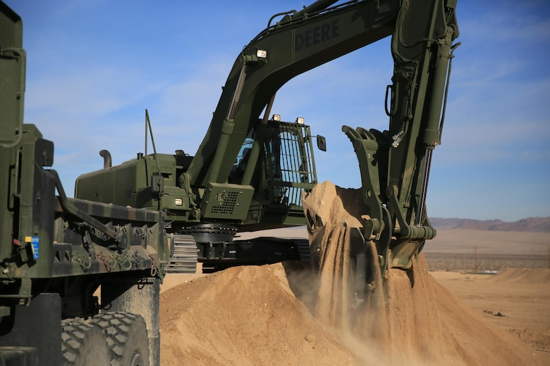 Staff Sgt. John Vasquez, heavy equipment operations chief, Marine Wing Support Squadron 374, scoops sand with a John Deere 250 GR Hydraulic Excavator near the Strategic Expeditionary Landing Field, Jan. 22, 2016. Marines with MWSS-374 and MWSS-371 attended the two-week maintainer and operator courses, Jan. 11-22. (Official Marine Corps Photo by Cpl. Julio McGraw/Released)