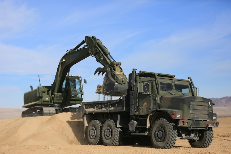 Staff Sgt. John Vasquez, heavy equipment operations chief, Marine Wing Support Squadron 374, scoops sand into a Medium Tactical Vehicle Replacement with a John Deere 250 GR Hydraulic Excavator near the Strategic Expeditionary Landing Field, Jan. 22, 2016. This is the first time MWSS-374 is using this excavator aboard the Combat Center and it is capable of utilizing interchangeable attachments to fulfill critical engineering missions. (Official Marine Corps Photo by Cpl. Julio McGraw/Released)