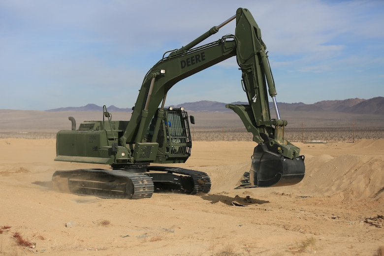 Staff Sgt. John Vasquez, heavy equipment operations chief, Marine Wing Support Squadron 374, maneuvers a John Deere 250 GR Hydraulic Excavator near the Strategic Expeditionary Landing Field, Jan. 22, 2016. The excavator enables Marines to fulfill critical engineering missions, including backhoe excavations, development of field fortifications, digging water and sewer lines, emplacement of culverts in-road, airfield construction and creating command bunkers. (Official Marine Corps Photo by Cpl. Julio McGraw/Released)