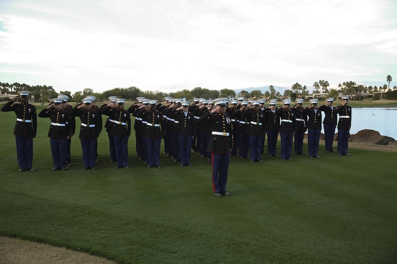 A formation of more than 50 Marine Corps Communication-Electronics School students led by Gunnery Sgt. Antonio Soto, company first sergeant, MCCES, salute during the presentation of the national colors and the playing of 'The Star-Spangled Banner' during the Career Builder Challenge Military Appreciation Ceremony at the Tom Weiskopf Private Course located in the Professional Golfers Association of America Course West in La Quinta, Calif., Jan. 23, 2016. (Official Marine Corps photo by Cpl. Medina Ayala-Lo/Released)