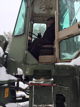A worker takes a short break from removing snow.