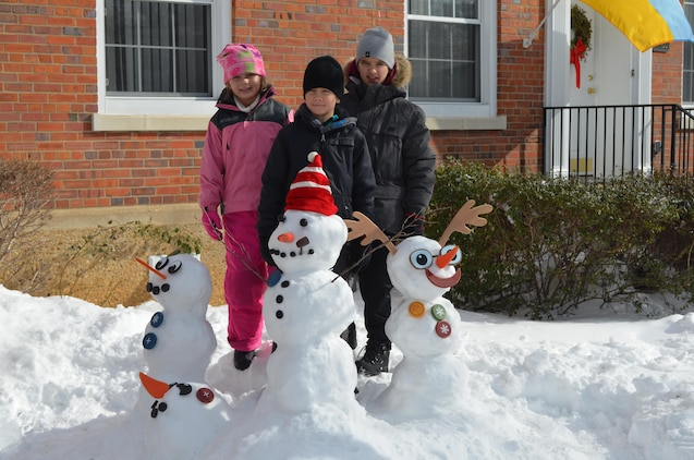 Kaitlyn, 8, Victor, 9, and Igor, 10, pose with their snow creations on Monday, as they enjoy the day off from school.