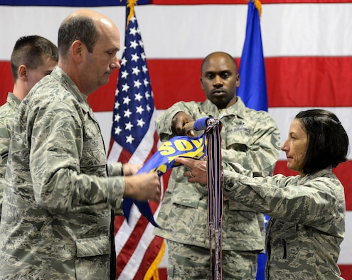 Col. Trevor Flint, 90th Maintenance Group commander, and Maj. Jacquie Sartori, 790th Maintenance Squadron commander, furl the recently inactivated 90th Maintenance Operations Squadron guidon Jan. 17, 2016, in the 90th MXG Maintenance High Bay on F.E. Warren Air Force Base, Wyo. The 90th MOS was redesignated to the 790th MXS. (U.S. Air Force photo by Senior Airman Jason Wiese)