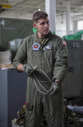 Sgt. Chris McClellan, KC-130J Super Hercules crew master with Marine Aerial Refueler Transport Squadron (VMGR) 152 at Marine Corps Air Station Iwakuni, Japan, discusses proper inspection of Y-cables prior to their use in an air drop kit, Jan. 26, 2016. McClellan taught a handful of crew masters and students the importance of gear check inspections while reviewing the nomenclature and uses of equipment in an air drop kit.