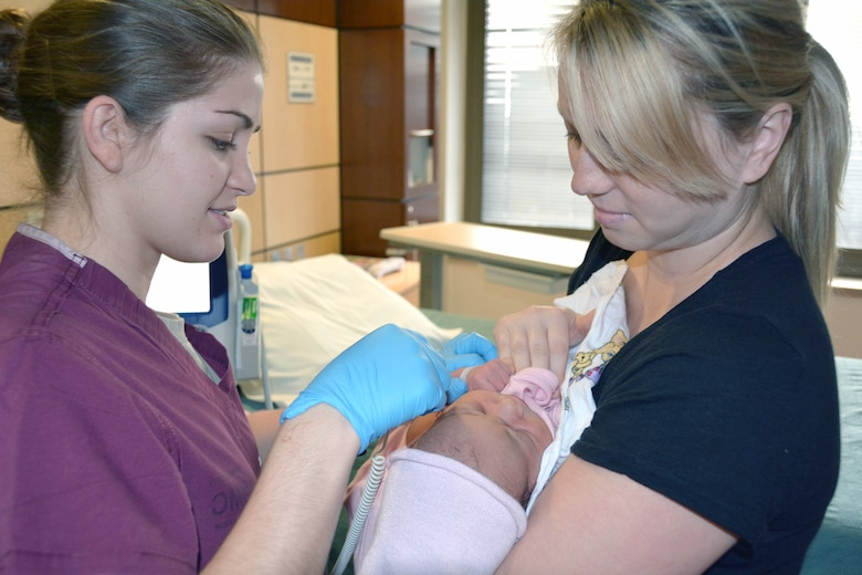 Air Force 2nd Lt. Auriel Vokolek, a nurse, takes newborn Isabella's temperature as her mom, Air Force Staff Sgt. Keri Sorsby, holds her in the post-partum unit at San Antonio Military Medical Center. (U.S. Army photo by Robert T. Shields/Released)